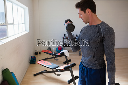 male athlete flexing muscles in gym