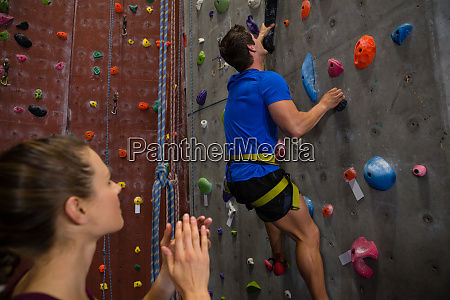 female athlete cheering trainer climbing wall