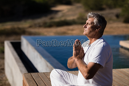 man practicing yoga on wooden plank