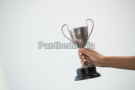 hand holding a trophy against white