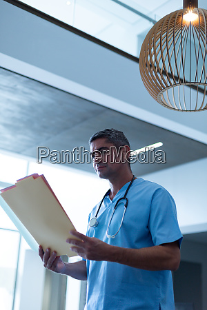 male surgeon looking at medical report