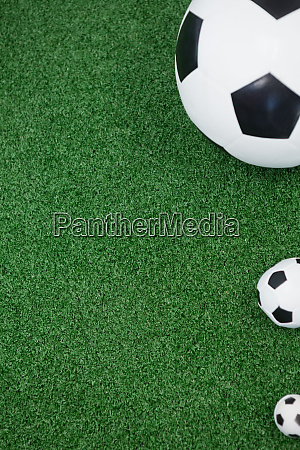 various size of footballs on artificial