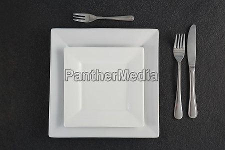 square plates and cutlery set on