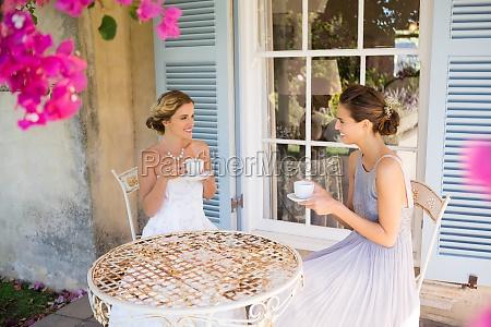 bride and bridesmaid having coffee in