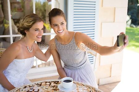 bridesmaid taking selfie with bride in