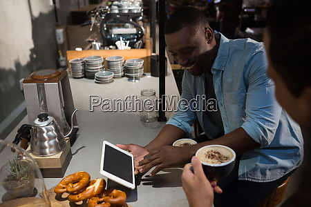 man using digital tablet while having