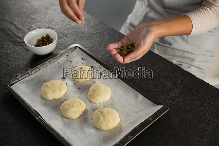 woman adding dry fruits over unbaked