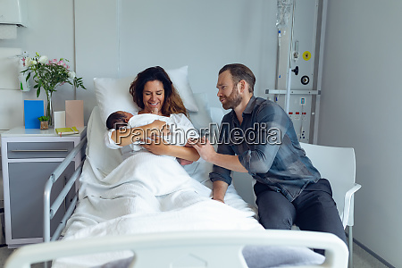 couple holding their newborn baby in