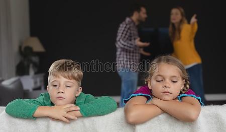sad kids leaning on sofa while