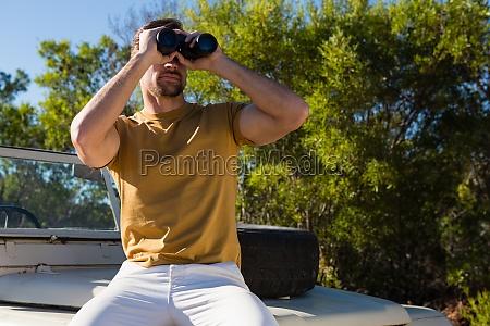 man looking through binocular on off