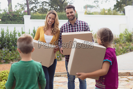 happy caucasian family holding cardboard boxes
