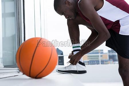 basketball player tying shoelace