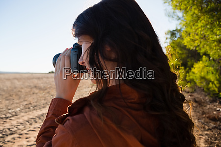 woman photographing from camera on field