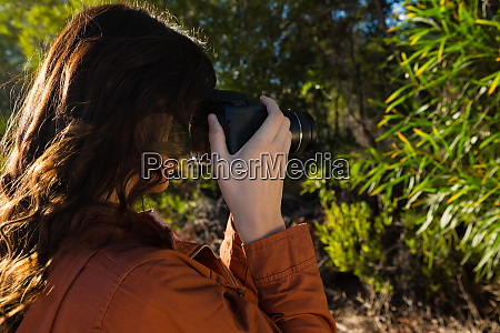 woman photographing trees