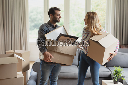 couple holding cardboard box in new