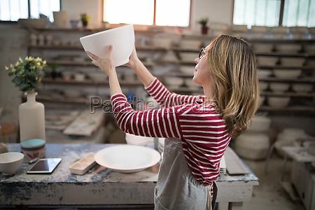 female potter checking bowl