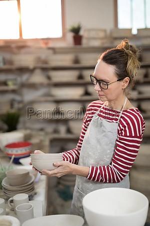 female potter holding stack of bowls