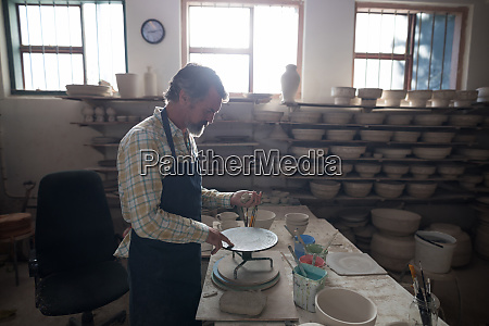 male potter molding a clay on