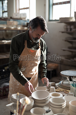 male potter working at worktop