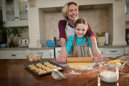 mother and daughter rolling dough with