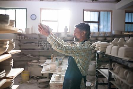 male potter checking bowl