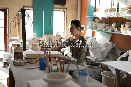 female potter working at worktop
