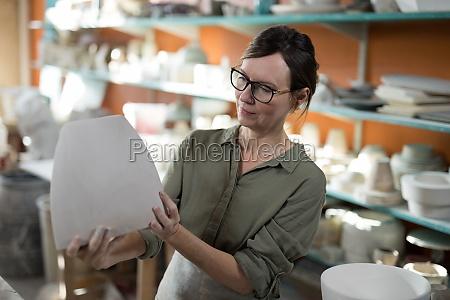 female potter checking ceramic vase