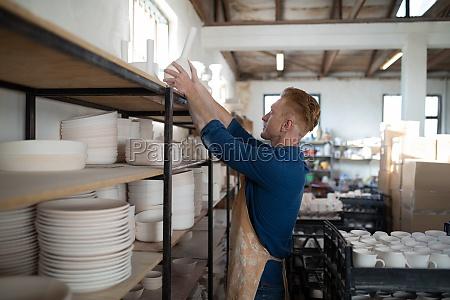 male potter placing vase on shelf