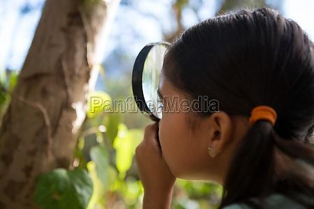 little girl holding magnifying glass exploring