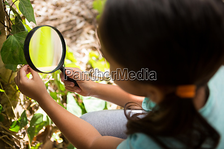 little girl exploring nature through magnifying