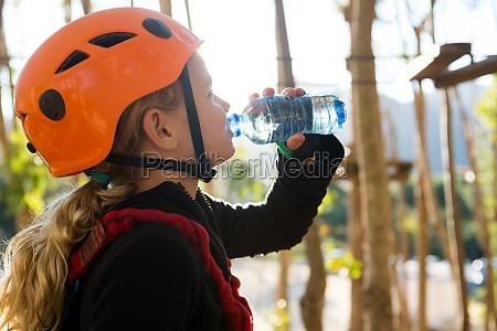 little girl wearing helmet drinking water