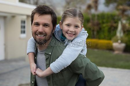 young girl rides piggyback