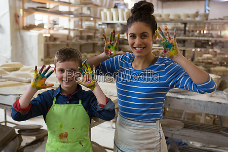 mother and son showing colorful paint