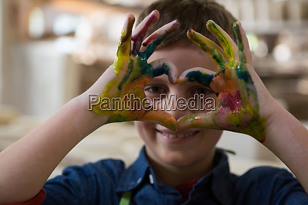 boy gesturing with painted hands
