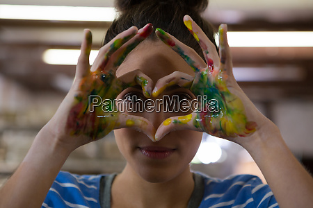 female potter gesturing with painted hands