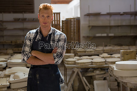 male potter standing with arms crossed