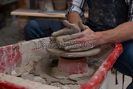 male potter making a pot in