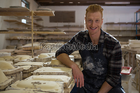 male potter smiling in pottery workshop