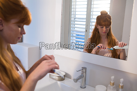 woman applying toothpaste on toothbrush in