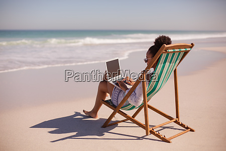 woman sitting on beach chair and