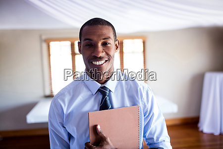 male supervisor standing with a file