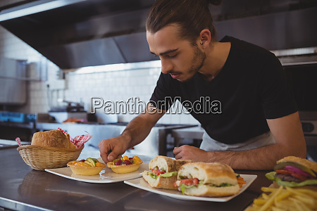 waiter arranging food in plate at