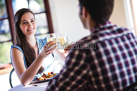couple toasting white wine glass in