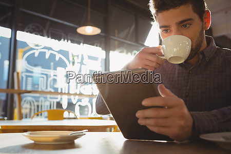 man drinking coffee while using tablet