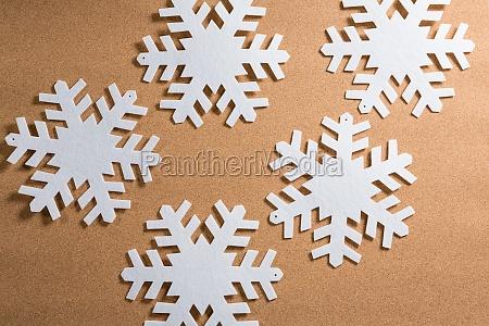 white snowflakes on brown background