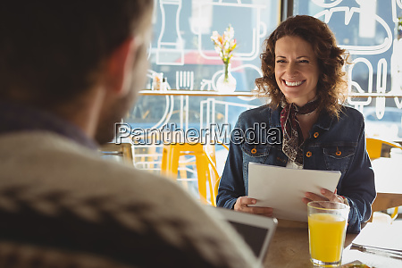 woman with document looking at man