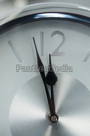 clock hands reaching 12 oclock midnight