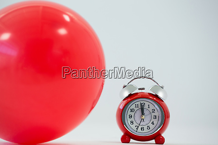 red balloon and alarm clock on