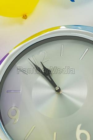 balloon and clock hands reaching 12