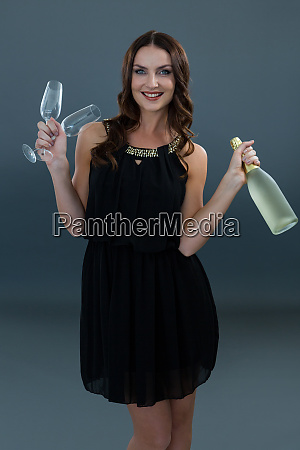 smiling woman holding champagne bottle and